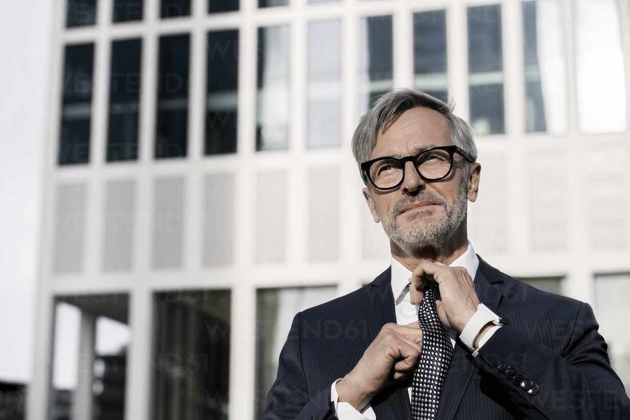 Grey-haired businessman adjusting his tie in front of skyscraper - SBOF00774 - Steve Brookland/Westend61