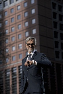 Grey-haired businessman in front of red skyscraper looking at his smartwatch - SBOF00777