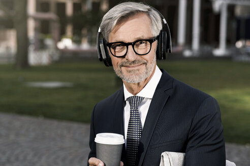 Grey-haired businessman with headphones and coffee to go looking into camera - SBOF00783