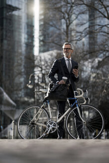 Grey-haired businessman with bicycle and coffee to go in the city - SBOF00786