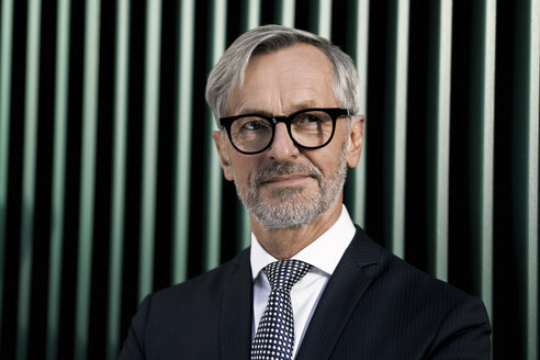 Portrait of grey-haired businessman in front of green wall - SBOF00789