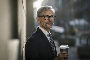 Grey-haired businessman in the city holding coffee to go - SBOF00792