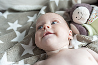 Portrait of smiling baby girl lying on a blanket - CSTF01401