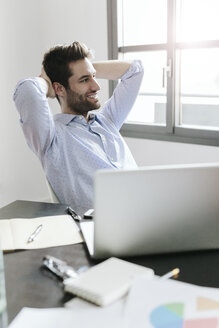 Young businessman working in office, taking a break - GIOF03254