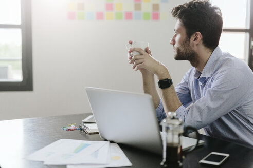 Young businessman working in office, drinking coffee - GIOF03275