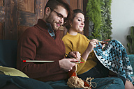 Young couple knitting and crocheting in living room - RTBF01009