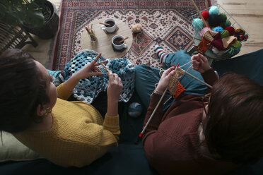 Young couple knitting and crocheting in living room - RTBF01012