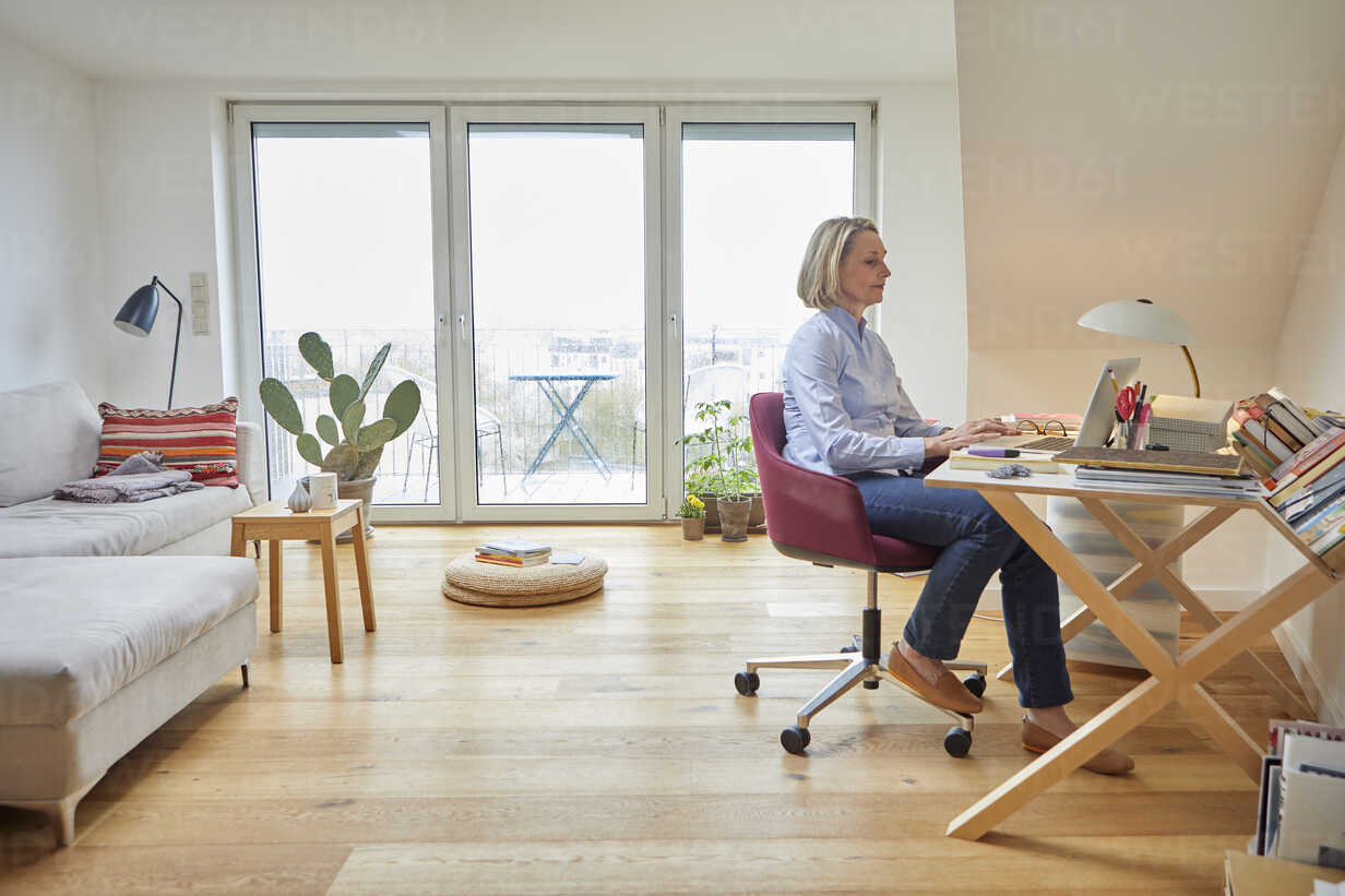 Mature woman at home using laptop at desk - RBF06027 - Rainer Berg/Westend61