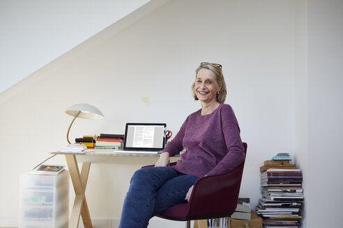 Portrait of smiling mature woman at home with laptop at desk - RBF06030