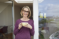 Portrait of smiling mature woman holding coffee mug on balcony - RBF06033