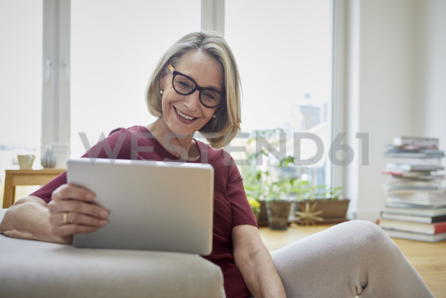 Smiling mature woman at home using tablet on the sofa - RBF06036