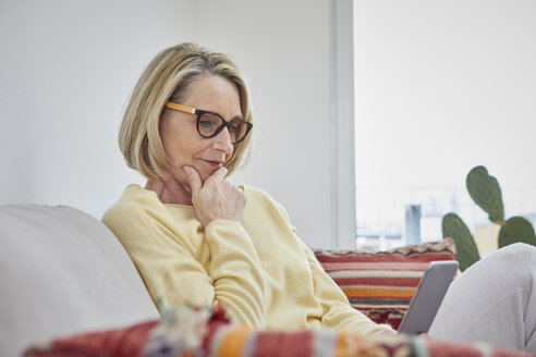 Mature woman at home looking at cell phone on the sofa - RBF06042