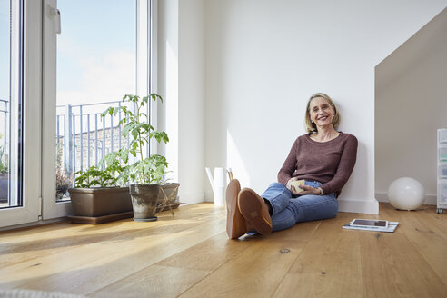 Portrait of smiling mature woman at home sitting on the floor - RBF06048
