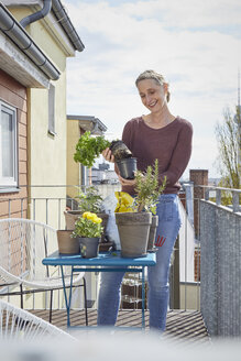 Smiling mature woman caring for plants on balcony - RBF06051