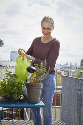 Smiling mature woman caring for plants on balcony - RBF06054