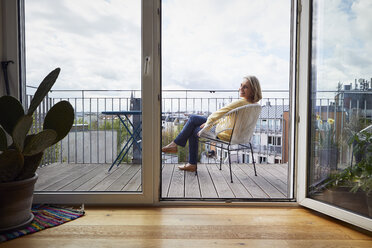 Smiling mature woman at home sitting on balcony - RBF06057