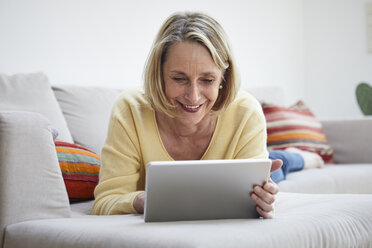 Smiling mature woman at home using tablet on the sofa - RBF06060