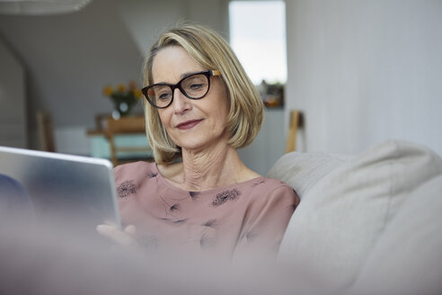 Mature woman at home using tablet on the sofa - RBF06063