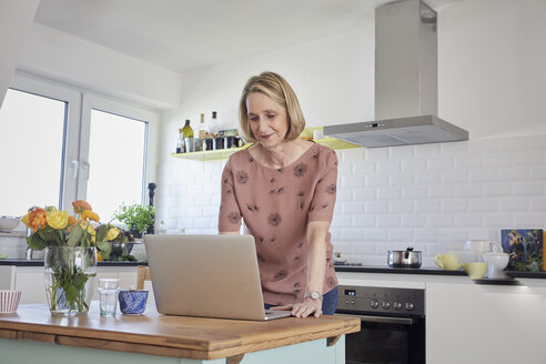 Mature woman at home using laptop in kitchen - RBF06069