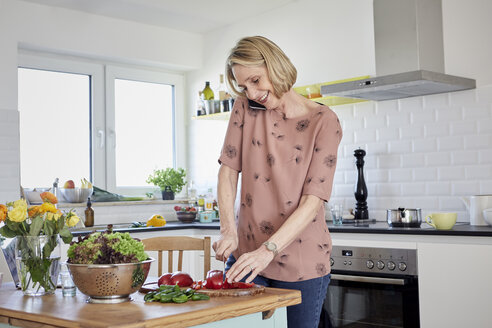 Mature woman preparing a salad and talking on the phone in kitchen - RBF06072