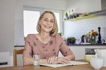 Portrait of smiling mature woman with notebook at kitchen table - RBF06075