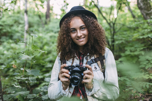 Portrait of smiling teenage girl taking pictures in nature - VPIF00096