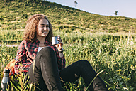 Teenage girl with thermos flask having a rest in nature - VPIF00108