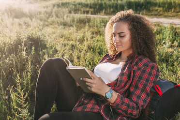 Teenage girl reading book on a meadow - VPIF00111