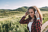Teenage girl listening music with headphones in nature - VPIF00114