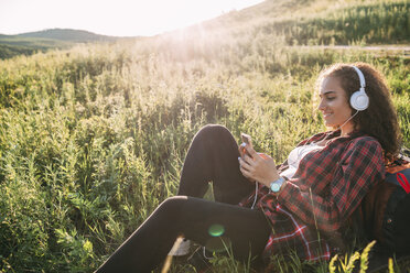 Teenage girl listening music with headphones on a meadow looking at cell phone - VPIF00117