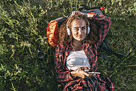 Teenage girl with backpack lying on a meadow listening music with headphones and cell phone - VPIF00120