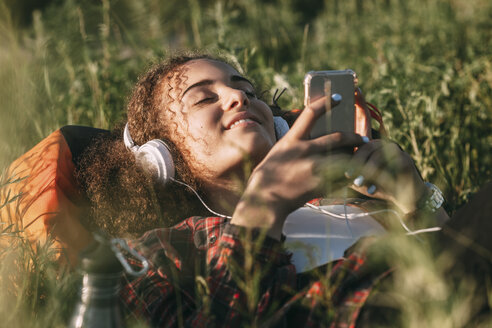 Teenage girl with backpack lying on a meadow listening music with headphones and cell phone - VPIF00123