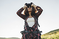 Teenage girl with backpack using binoculars in nature - VPIF00132