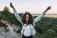 Happy teenage girl with smartphone and backpack in nature - VPIF00138