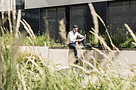 Businessman sitting on wall outside office building reading document - UUF11689