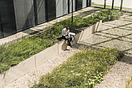Businessman sitting on bench outside office building using tablet - UUF11692