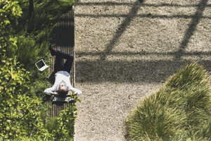 Businessman with headphones lying on a bench next to tablet - UUF11695