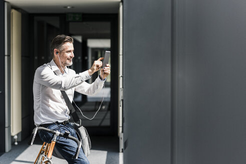 Businessman with bicycle in office passageway using cell phone - UUF11698