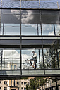 Businessman with cell phone and bicycle in office passageway - UUF11701