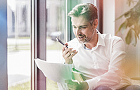 Businessman looking at documents using cell phone - UUF11707