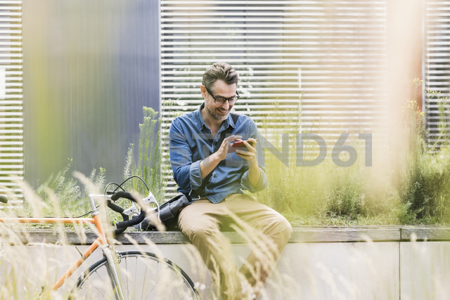 Smiling businessman using cell phone next to bicycle - UUF11725