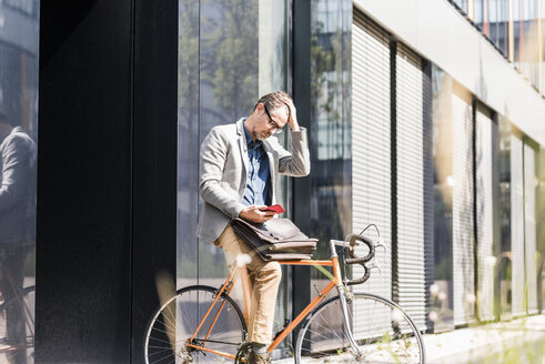 Shocked businessman on bicycle looking at cell phone - UUF11728