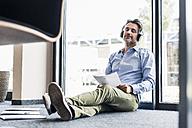 Businessman with headphones sitting on the floor in office - UUF11731