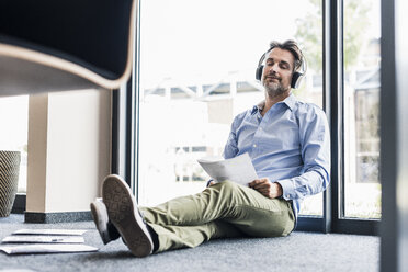 Businessman with headphones sitting on the floor in office - UUF11731