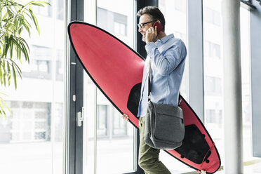 Smiling businessman on cell phone carrying surfboard - UUF11734