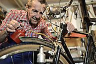 Senior man oiling bicycle in his workshop - ECPF00126