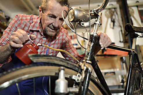 Senior man oiling bicycle in his workshop - ECPF00126