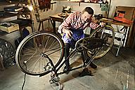 Senior man checking bicycle in his workshop - ECPF00129