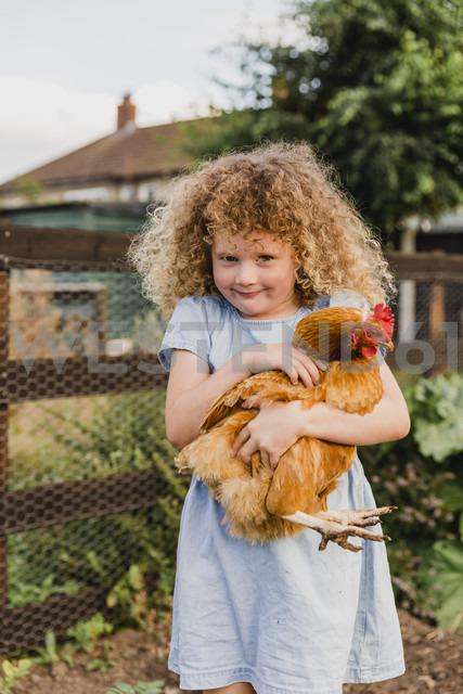 Smiling girl hugging hen - NMSF00155