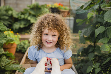 Portrait of happy little girl feeding chickens in allotment - NMSF00158